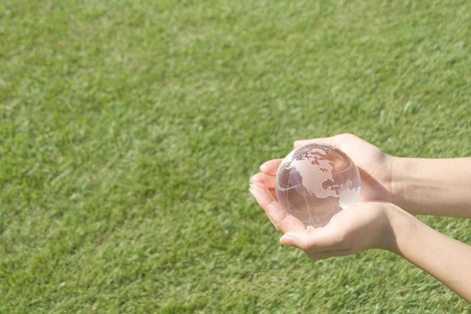 芝生で水晶玉を持つ女性の手